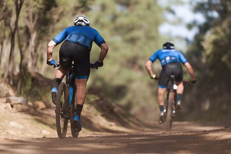 Athletes mountain biking on forest trail, mountain bike race Reklamní fotografie - 142389223