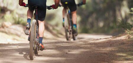 Athletes mountain biking on forest trail, mountain bike race Reklamní fotografie - 143531149