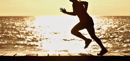 Woman running on beach in morning sunrise, fitness workout sport Reklamní fotografie - 144725207