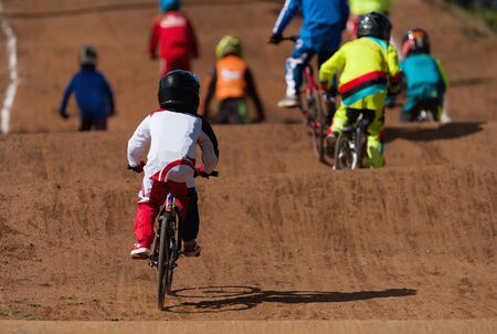 BMX riders competing in the child class on the off-road circuit Reklamní fotografie - 145743182