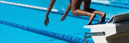 The swimmer jumps from the start block at the start of the race Reklamní fotografie