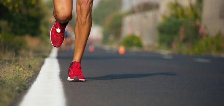 Fast strong runner feet running on asphalt road close up in sport shoe