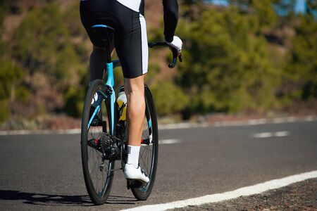Road bike cyclist man cycling. Biking sports fitness athlete riding bike on an open road, active healthy sports lifestyle athlete cycling Reklamní fotografie - 146570014