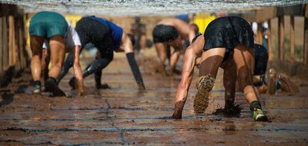 Runners crawling under a barbed wire in a test of the race, extreme obstacle race Reklamní fotografie - 146569685