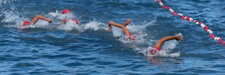 Group of swimmers swim in the sea at the races, open water sport