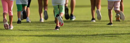 Running children, young athletes run in a kids run race, running on grass detail on legs, running in the light of morning Reklamní fotografie