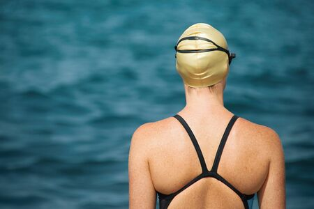 A swimmer stands on the shore of the ocean concentrated for a competition Reklamní fotografie - 147585910