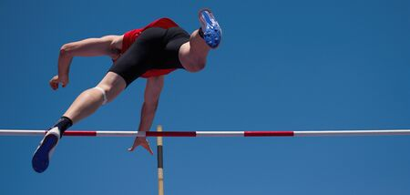Competition pole vault jumper male on blue sky background