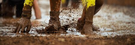 Mud race runners.Crawling,passing under a barbed wire obstacles during extreme obstacle race 版權商用圖片