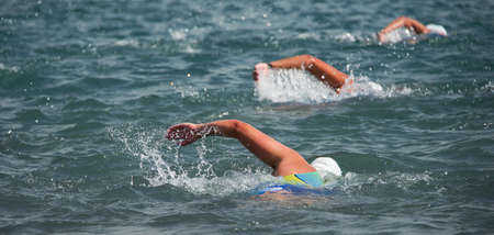 Triathlon swimmers churning up the water three swimmers in races in triathlon Stock Photo