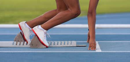 Woman in a starting block on an athletic field Foto de archivo