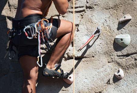 Sportsman climber moving up on steep rock, climbing on artificial wall outdoors. Extreme sports and bouldering concept Stock Photo