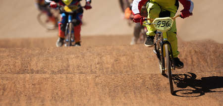 BMX riders competing in the child class on the off-road circuit Stock Photo