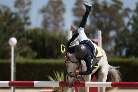 Horse show jumping accident, young rider falling from horse during a competition
