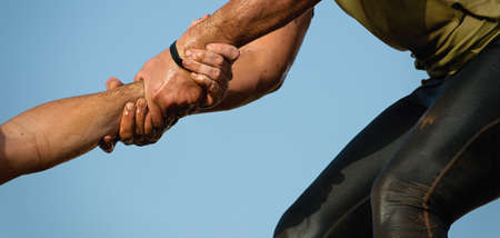 Mud race runners. Couple hold hands, help when overcoming hindrances mud