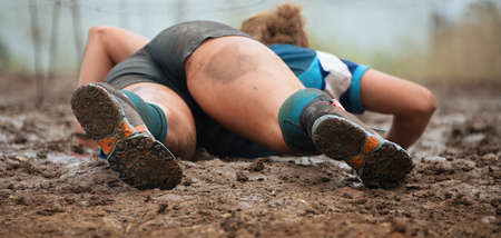 Mud race runners. Crawling, passing under a barbed wire obstacles during extreme obstacle race 免版税图像