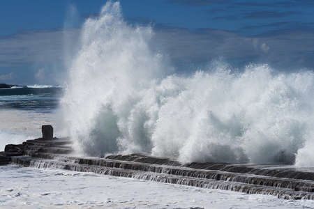 A great wave crashing on a day of rough ocean