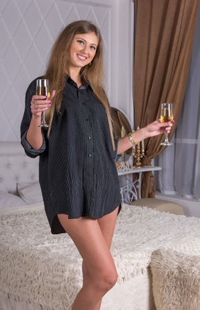 girl with two glasses of wine by the bed