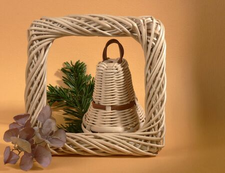 nontraditional: Still life with one wicker Christmas bell on orange background Stock Photo