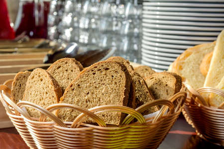 breadbasket: Fresh sliced bread in a wicker basket on the background of cookware Stock Photo