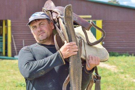 man carries a rider saddle for your horse