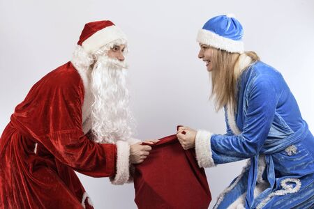 grandfather frost: cheerful Santa Claus and snow maiden taking each others bag of gifts Stock Photo