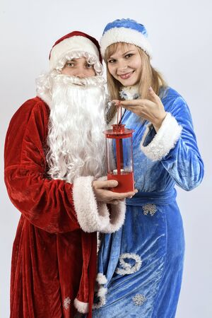 snegurochka: Cheerful Santa Claus with the snow maiden holding a Christmas lamp