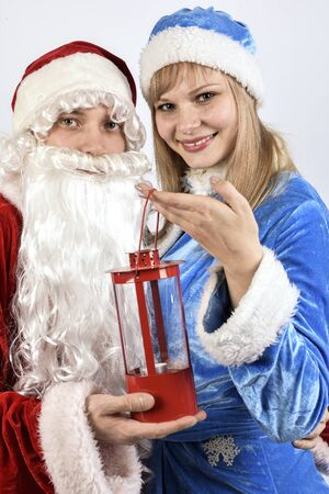 snegurochka:  Cheerful Santa Claus with the snow maiden holding a Christmas lamp Stock Photo