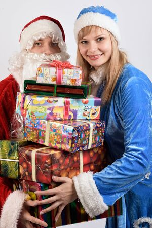stagy: Santa Claus and snow maiden holding a Christmas gift