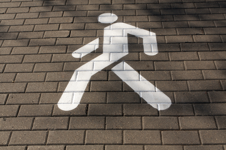 White pedestrian sign on pavement. Road and signs.