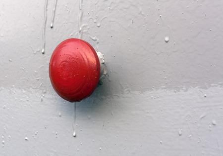 Rode knop op grijze metalen muur. Achtergrond en textuur. Stockfoto