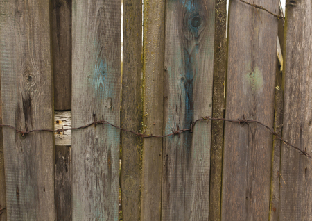 barbed wire fence: Barbed wire on old wooden fence. Architectural background. Stock Photo