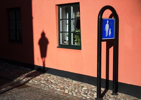 Pedestrian sign near orange building. Urban background.