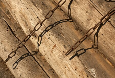 rusty chain: Rusty metal chain on log barn wall. Abstract background