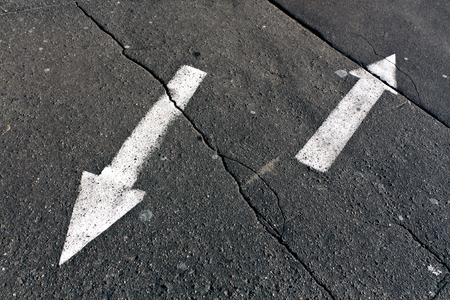 two arrows: Two arrows on cracked asphalt surface. Urban background. Stock Photo