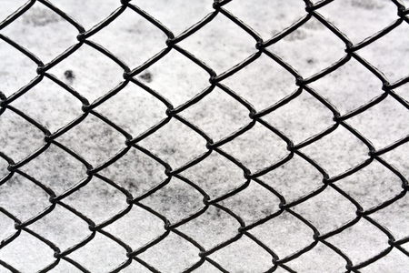 Wire fence and snow texture. Seasonal background Stock Photo