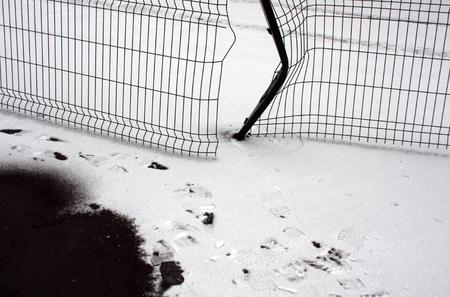 Brocken metal fence and snow. Seasonal background Stock Photo