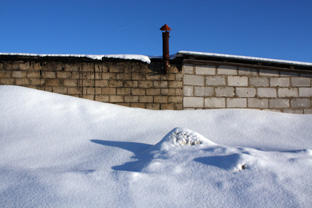 tile wall: Old brick building and snow pile. Seasonal background. Stock Photo