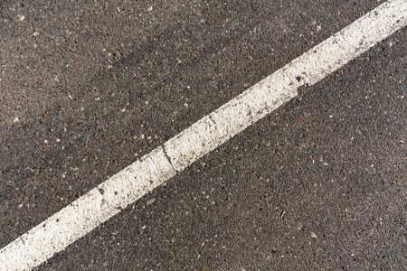 rules: White line on gray asphalt surface. Traffic signs. Stock Photo