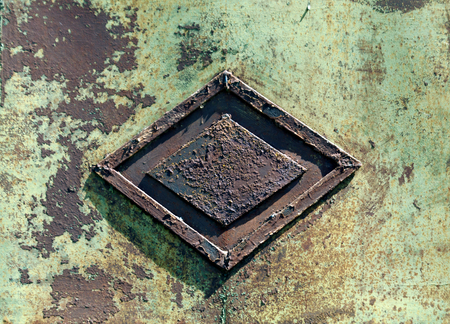pitting: Rusty metal gate with rhombus decoration. Background and texture for design.