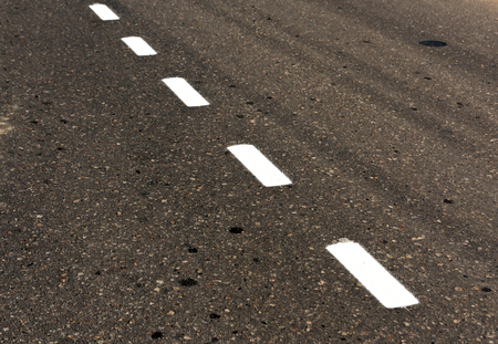 White road line on dirty asphalt texture. Background and texture for design.