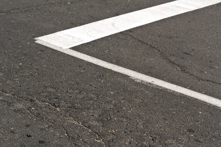 White paint mark on the old asphalt road. Traffic marks and signs. Stock Photo