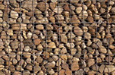 gabion: Pile of stones behind metal grid.