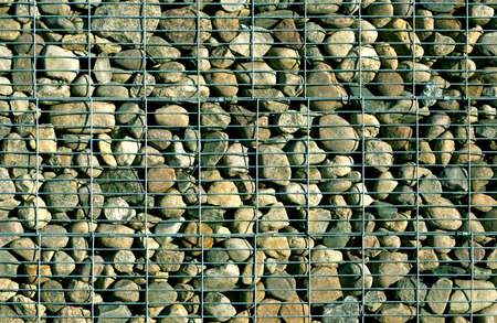 metal grid: Pile of stones behind metal grid.