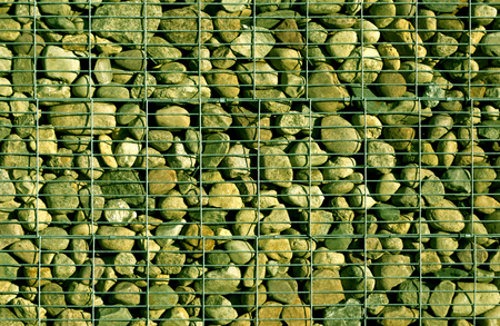 gabion mesh: Pile of stones behind metal grid.