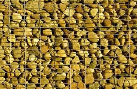 metal grid: Pile of stones behind metal grid.