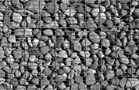 gabion mesh: Pile of stones behind metal grid. Background and texture for design. Stock Photo
