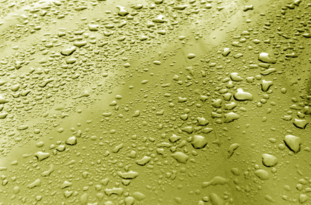 metal textures: Rain drops on yellow metal surface. Background and textures. Stock Photo