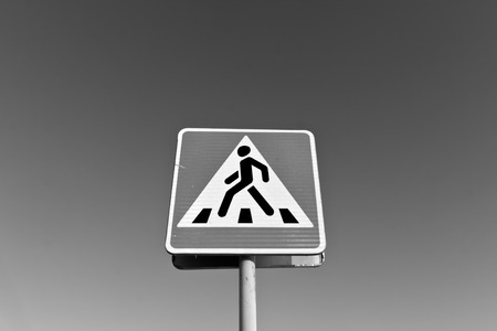 Metal pedestrian sign in black and white. Road and signs.