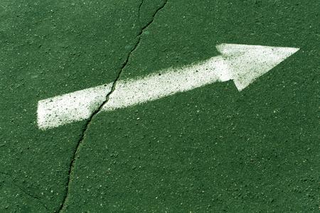 White arrow on green asphalt surface. Urban background.